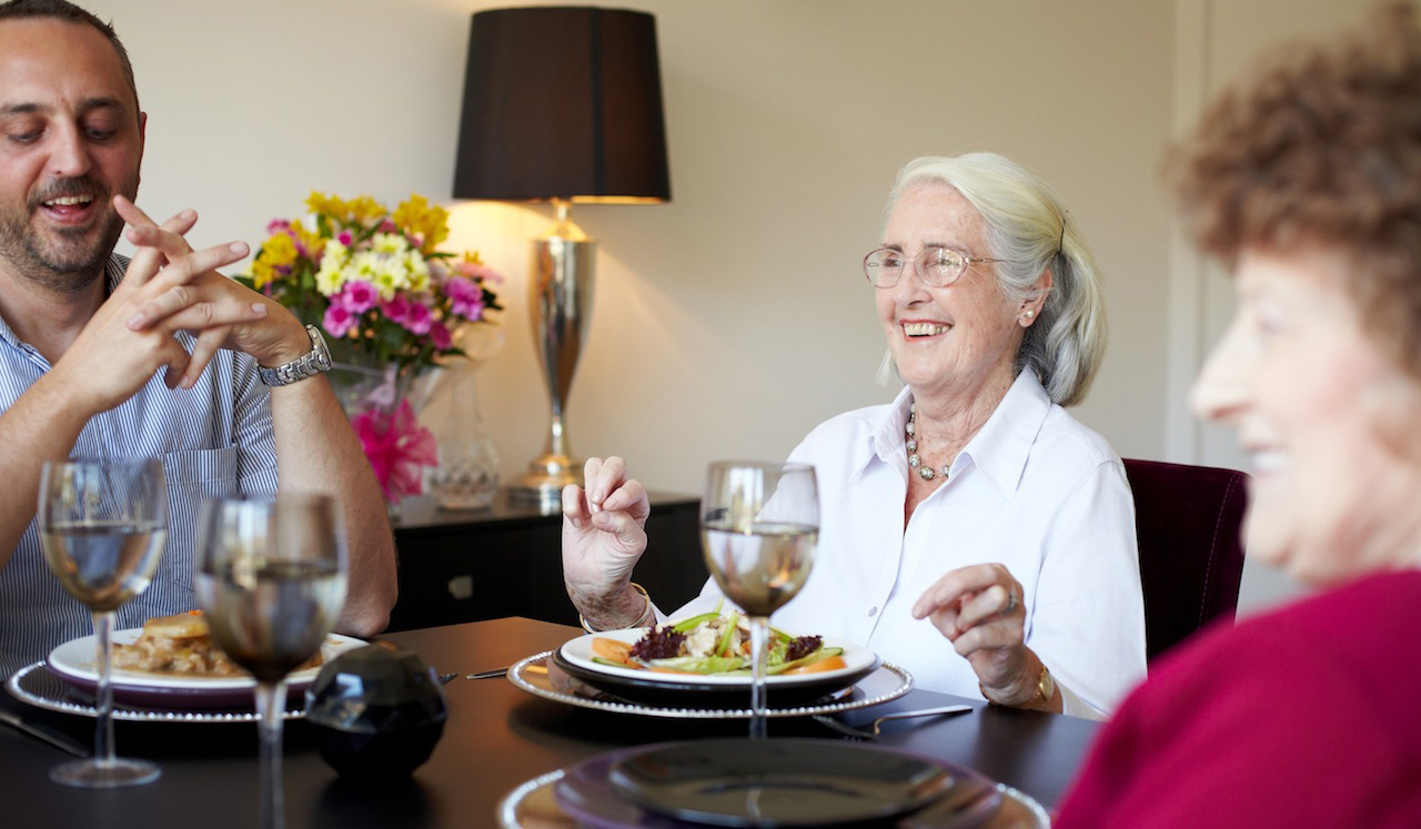 Three residents enjoy a relaxed evening meal